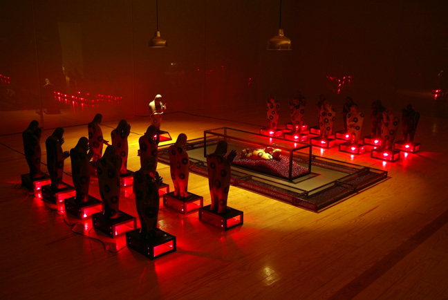 """CARLOS RUNCIE TANAKA, """"Tiempo detenido / No Olvidar"""", 1997-2006, Variable dimensions, Installation - 22 ceramic figures, 11 glass/metal cases with red light, 10 glass/metal cases containing red marbles, 1 glass/metal urn containing 1 ceramic figure and three lamps hanging from the ceiling in a room with inner walls covered completely by glass panels. Taking inspiration from his hostage experience at the Japanese Ambassador's Residence where he was held captive with many others by the MRTA (Movimiento Revolucionario Túpac Amaru) in Lima, December 1996, the artist creates this installation with allusions to violence and the lack of communication. Time detained – Do not forget"""